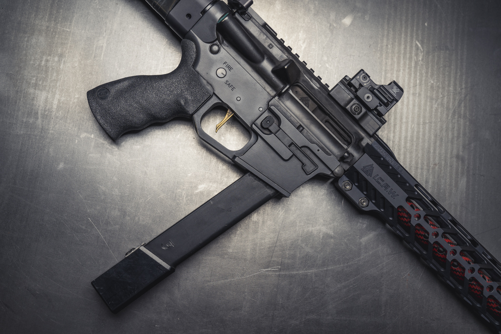 a PCC with upgrades such as a match trigger, red dot, extended magazine, and carbon fiber barrel