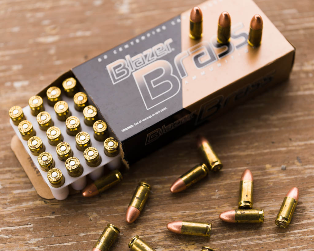 a box of Blazer Brass 9mm FMJ opened with rounds laying on the table