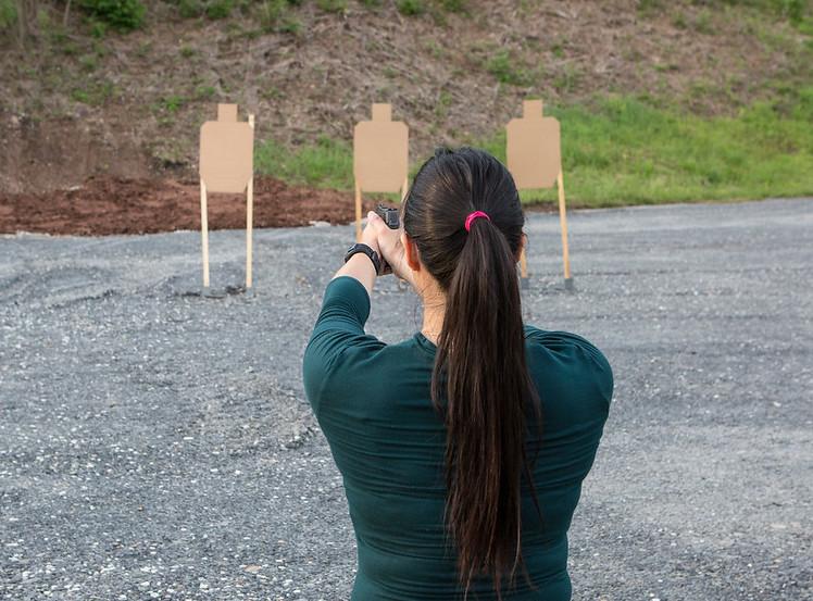 Demonstrating upper body pistol shooting position for recoil management